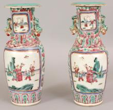 A PAIR OF 19TH CENTURY CHINESE FAMILLE ROSE CANTON PORCELAIN VASES, each painted with figural garden terrace panels, 9.8in high.