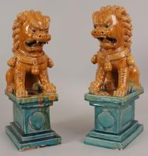 A PAIR OF LARGE 20TH CENTURY CHINESE GLAZED POTTERY MODELS OF TEMPLE GUARDIAN LIONS, each applied in turquoise and ochre glazes and seated on a rectangular section plinth, 6.9in x 4.5in at base & 13.3in high. <br>