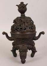 A GOOD 18TH CENTURY CHINESE QIANLONG PERIOD BRONZE ELEPHANT TRIPOD CENSER & COVER, weighing 1.7Kg, with good patination, the pierced lotus cover with a reclining elephant bearing a vase upon its back, the feet in the form of elephant's heads, a very few stone insets remaining, 7.4in wide including handles & 10.2in high overall.