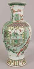A LARGE EARLY 20TH CENTURY CHINESE FAMILLE VERTE PORCELAIN VASE, the sides of the baluster form body painted with a figural garden scene, 17.2in high.