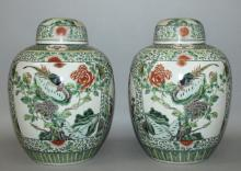 A GOOD MIRROR PAIR OF LATE 19TH CENTURY CHINESE FAMILLE VERTE PORCELAIN JARS & COVERS, each painted with a large panel of a pheasant perched on rockwork beside flowering peony and with a large river landscape panel, the panels divided by small circular panels of foliage, the panels reserved on a formal ground of scroll-stemmed flowerheads, 12.75in high overall.
