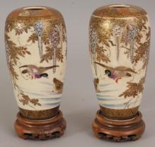 A MIRROR PAIR OF EARLY 20TH CENTURY JAPANESE SATSUMA EARTHENWARE VASES, together with wood stands, each painted with a pair of ducks beneath overhanging wisteria, 5.75in high overall on stands, the vases themselves 5in high.