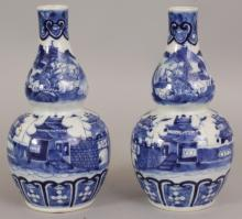 A GOOD PAIR OF 19TH CENTURY CHINESE BLUE & WHITE DOUBLE GOURD PORCELAIN VASES, each painted with a walled settlement in a mountainous landscape, each base with a four-character Kangxi mark, 7.25in high.