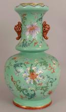 A FINE QUALITY EARLY 19TH CENTURY CHINESE LIME GREEN GROUND FAMILLE ROSE PORCELAIN VASE, the ovoid body rising to a waisted neck moulded with pierced elephant form handles painted in iron-red and gilding, the sides and neck of the vase painted with formal arrangements of European inspired flowerheads and scrolling stems reserved on an incised sgraffito ground, the rounded neck rim with a ruyi border, 15.5in high.