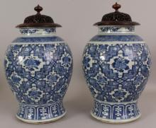A LARGE PAIR OF 19TH CENTURY CHINESE BLUE & WHITE PORCELAIN VASES, with good quality carved and pierced fitted hardwood covers, the sides painted with an unusual formal foliate design between formal borders, 17in high overall, each vase itself 13.7in high.