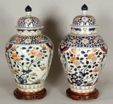 A GOOD LARGE PAIR OF EARLY JAPANESE IMARI PORCELAIN VASES & COVERS, circa 1700, together with fitted wood stands, the sides painted with panels of flowers and of blossoming boughs, some flowerheads moulded in relief, 29.5in high overall on stands, the vases themselves 27.25in high overall.