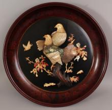 A JAPANESE MEIJI PERIOD ONLAID LACQUER DISH, circa 1900, the interior decorated in onlaid bone ivory and mother-of-pearl with a pair of pigeons perched on a blossom bearing bough, 17.75in diameter.