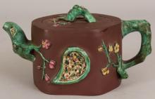 A 19TH CENTURY CHINESE ENAMELLED YIXING POTTERY TEAPOT & COVER, the sides moulded in relief with a tear-form panel, a mask and sprigs of blossom in high relief, the underside of the cover and the base each with an impressed seal mark, 7.25in long & 4in high.