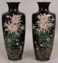 A PAIR OF GOOD QUALITY JAPANESE MEIJI PERIOD BLACK GROUND CLOISONNE VASES, each decorated in fine detail with an arrangement of flowerheads and leafage, 11.7in high.