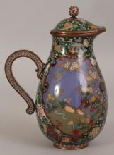A FINE QUALITY JAPANESE MEIJI PERIOD CLOISONNE JUG & HINGED COVER, some of the cloisons in silver-wire, the pear-form body decorated with detailed elaborately shaped opaque enamel panels of birds and foliage reserved on an unusual ground of scattered sea shells, flowerheads and waves over translucent green enamel, 4.6in long including handle & 6.5in high overall.