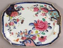 AN 18TH CENTURY CHINESE QIANLONG PERIOD FAMILLE ROSE PSEUDO TOBACCO LEAF PORCELAIN DISH, the interior painted with insects, scroll-form panels and floral sprays, the base unglazed, 13.5in x 10in at widest points.