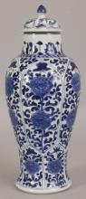 A CHINESE KANGXI PERIOD BLUE & WHITE PORCELAIN VASE, circa 1700, with fitted cover, the sides painted in a good tone of underglaze-blue with slightly moulded lappet panels of a butterfly above formal extended peony, the base with an artemisia leaf, 11.25in high overall.