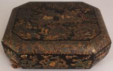 A GOOD 19TH CENTURY CHINESE LACQUERED WOOD GAMES BOX & COVER, of chamfered rectangular form, the interior fitted with numerous covered boxes and playing card trays, 14.6in x 12in x 5.1in high.