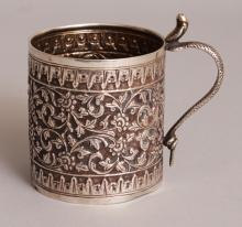 A SOUTH-EAST ASIAN SILVER-METAL TANKARD, weighing 130gm, with a snake-form handle, the sides embossed with formal scrolling foliage, 2.75in diameter at rim & 3.6in high to top of handle.