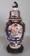 A JAPANESE IMARI MEIJI PERIOD OCTAGONAL SECTION PORCELAIN VASE & COVER, together with a carved wood stand, 15.75in high overall.