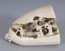 AN UNUSUAL JAPANESE IVORY OKIMONO OF A FRUIT POD, the interior to reveal a 'dream' of diminutive figures on riverboat and a river bank, 1.9in wide at widest point & 2.5in high.