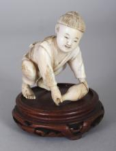 A JAPANESE MEIJI PERIOD IVORY OKIMONO OF A KNEELING BOY, mounted on a fixed wood base, the boy picking up a bottle, 2.9in high overall.