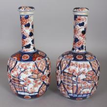 A PAIR OF JAPANESE MEIJI PERIOD IMARI FLUTED PORCELAIN BOTTLE VASES & COVERS, 10.25in high overall.