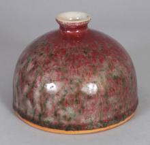 A CHINESE PEACH BLOOM PORCELAIN BEEHIVE WATER POT, the red streaked glaze with green inclusions, 4.5in diameter at base & 3.25in high.