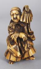 A JAPANESE MEIJI PERIOD STAINED IVORY OKIMONO OF A DANCER & HIS SON, the man holding an upturned fan, 2.9in high.