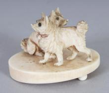 AN UNUSUAL SMALL JAPANESE MEIJI PERIOD IVORY OKIMONO OF TWO DOGS, on an oval plinth, 1.75in wide & 1.25in high.