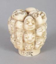AN EARLY 20TH CENTURY SIGNED JAPANESE IVORY CANE HANDLE, carved with a variety of masks, 1.7in high.