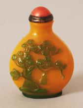 A CHINESE YELLOW GROUND GREEN OVERLAY GLASS SNUFF BOTTLE & CORAL STOPPER, decorated in relief with a pine tree and with a locust on a pea pod, 2.1in high.