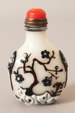 A CHINESE OVERLAY GLASS SNUFF BOTTLE & STAINED IVORY STOPPER, decorated in relief in white and aubergine with blossoming plants reserved on an opaque white ground, 2.5in high.