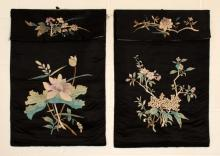 A PAIR OF 19TH/20TH CENTURY CHINESE BLACK GROUND SILK WALL HANGINGS, each decorated with a floral arrangement, each approx. 32.5in x 18.5in.