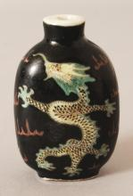 A CHINESE FAMILLE NOIRE PORCELAIN DRAGON SNUFF BOTTLE, 2.3in high.