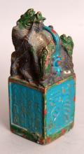 AN UNUSUAL CHINESE ENAMELLED BRONZE SEAL, surmounted by a group of dragons, 1.7in square & 4.3in high.