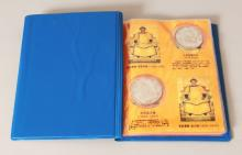 A CHINESE COMMEMORATIVE ALBUM OF TWELVE SILVER-METAL COINS.