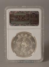 A CHINESE SILVER METAL COIN, in a presentation case, the coin itself 1.5in diameter.