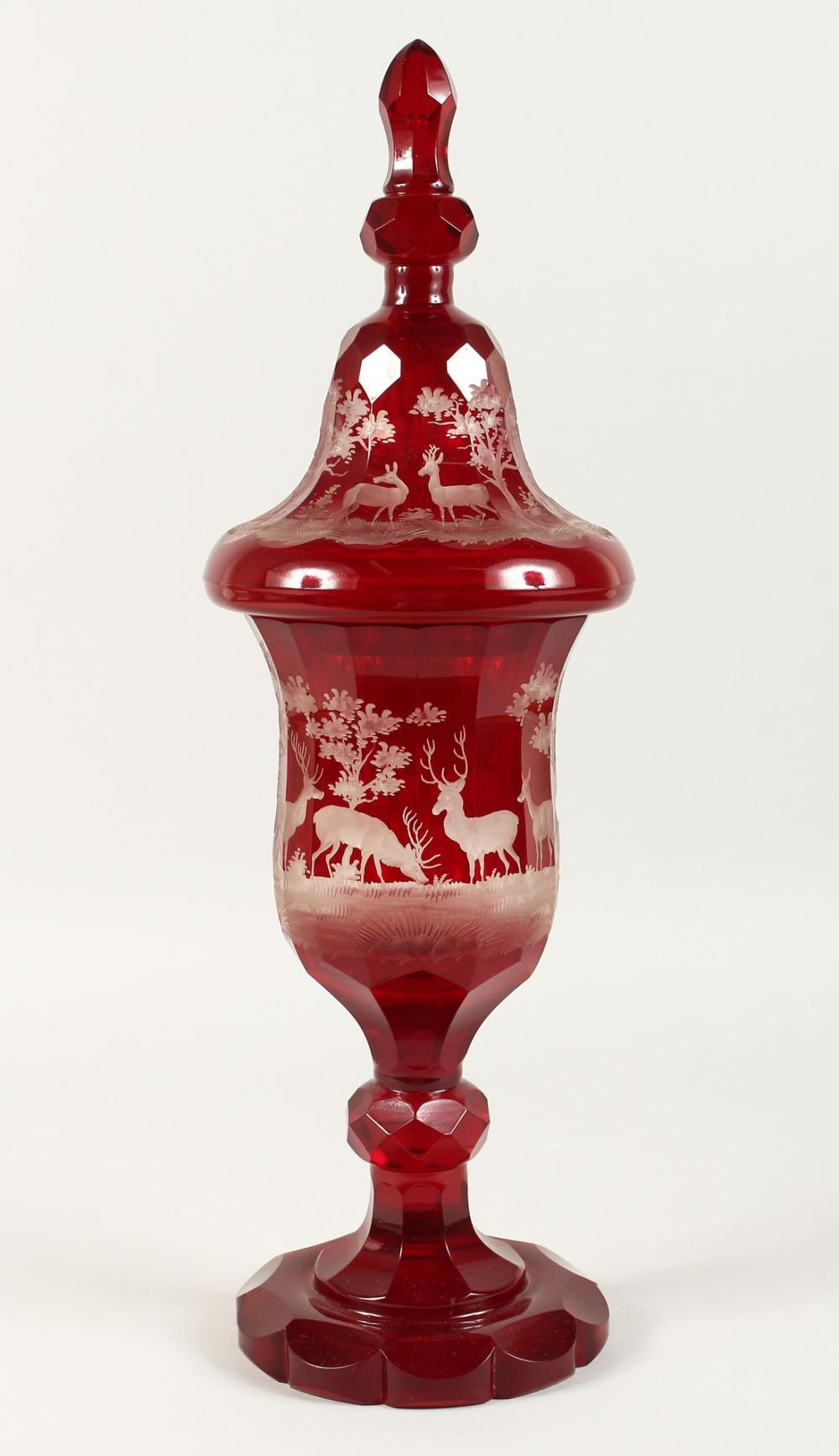 A SUPERB LARGE VICTORIAN BOHEMIAN RUBY GOBLET AND COVER etched with deer in a landscape. 20ins high.