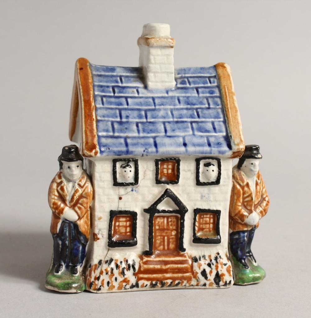 A 19TH CENTURY PRATTWARE MODEL OF A COTTAGE, with a male figure standing to each side. 4ins wide x 4.5ins