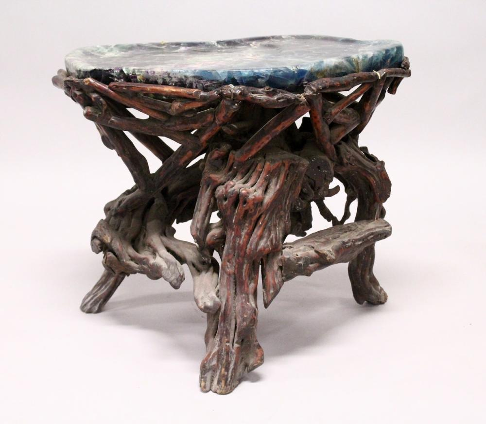 AN UNUSUAL FLOUROSPAR AND ROOTWOOD STAND OF NATURALISTIC DESIGN. 2ft wide x 1ft 8ins high.