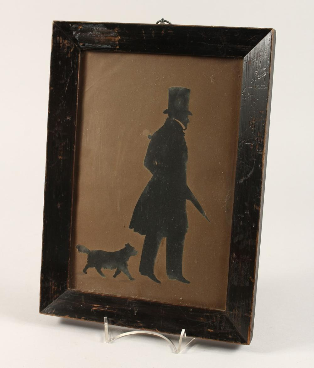A VICTORIAN FRAMED AND GLAZED SILHOUETTE OF A GENTLEMAN, with his dog. 10ins x6.5ins