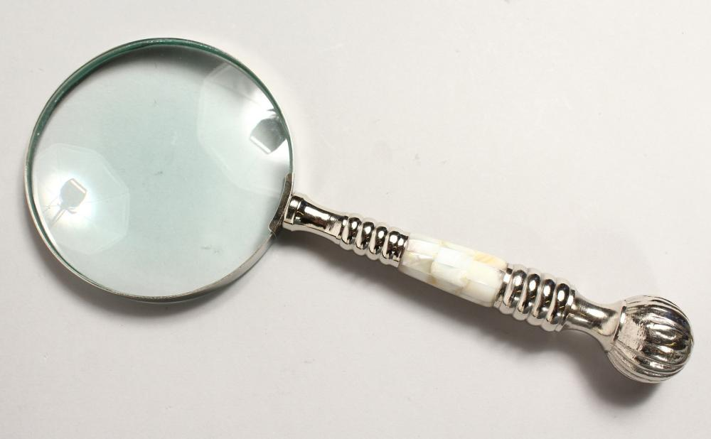A MAGNIFYING GLASS with mother of pearl and chrome handle.
