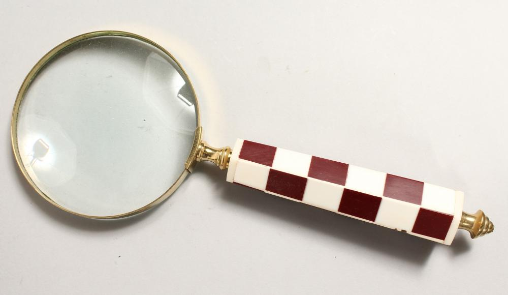 A MAGNIFYING GLASS with chequered handle.