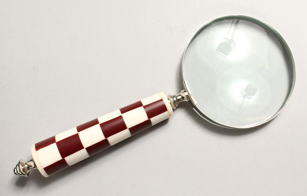 A MAGNIFYING GLASS with chequered handle