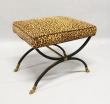 A BRONZE AND IRON CROSS FRAME STOOL with padded top. <br>1ft 9ins long x 1ft 4ins high.