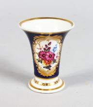 A MINIATURE CHAMBERLAIN'S WORCESTER VASE, CIRCA. 1800, blue ground edged in gilt and painted with flowers. <br>Printed Mark in Red. <br>2.5ins high.