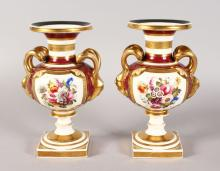 A GOOD PAIR OF ROCKINGHAM DESIGN TWO-HANDLED URN SHAPED VASES, CIRCA. 1840, with double loop, mask handles, painted reverse panels with flowers and supported on square bases. <br>9ins high.