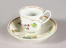 AN 18TH CENTURY WORCESTER COFFEE CUP AND SAUCER painted with flowers in an arabesque panel.