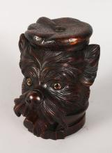 A BLACK FOREST DOG'S HEAD TOBACCO BOX, with lift off head and glass eyes. <br>7ins high.