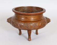 A CHINESE BRONZE CENSER, with lion mask handles, on three curving legs. <br>6ins wide.