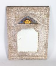 A GOOD PERSIAN SILVER MIRROR, the top with a panel painted with the top of a head and piercing eyes. <br>9ins x 6ins.