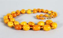 AN EGG YOLK/BUTTERSCOTCH AMBER BEAD NECKLACE, comprising 43 graduated beads with 9ct gold clasp, approx. 35gms.  75cms long.