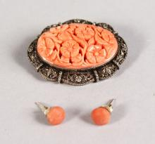 A CARVED CORAL AND SILVER OVAL BROOCH AND EARRINGS.