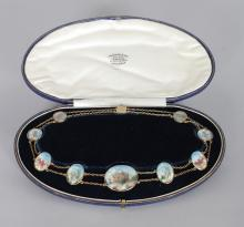 A SUPERB INDIAN GOLD PICTORIAL NECKLACE, set with nine oval plaques including TAJ MAHAL, in a blue leather box. <br>